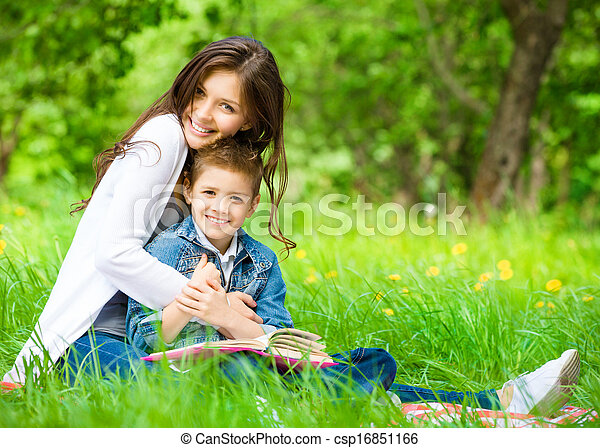 Mom and son with book in green park - csp16851166