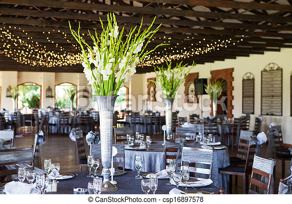 Wedding reception venue with decorated tables and fairy lights - csp16897578