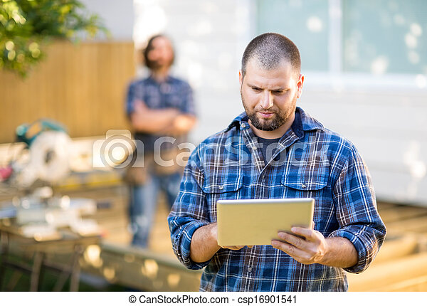 Mid adult manual worker using digital tablet with coworker standing in background at construction site - csp16901541