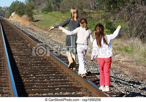 Girls walking on railroad tracks - csp1690256