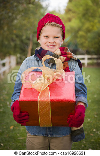Handsome Young Boy Wearing Holiday Clothing Holding Christmas Gift Outside. - csp16926631