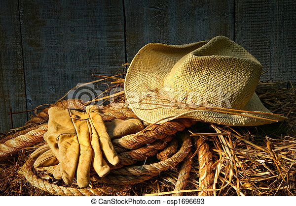 Straw hat with gloves on a bale of hay - csp1696693