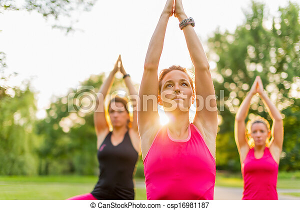 group of 3 women doing yoga in nature - csp16981187