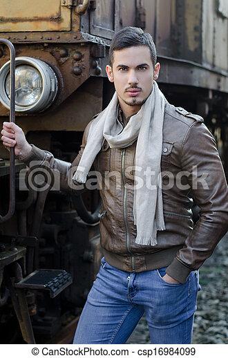 Attractive young man in leather jacket and jeans next to old train looking at camera - csp16984099