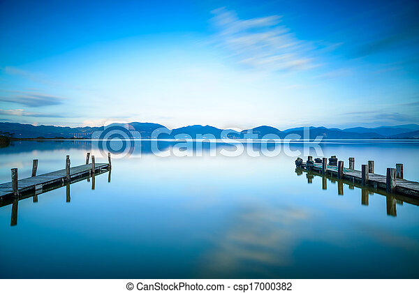 Two Wooden pier or jetty on a blue lake sunset and cloudy sky reflection on water. Long exposure, Versilia Massaciuccoli Lake, Tuscany, Italy. - csp17000382