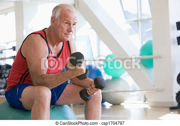 Man Using Hand Weights On Swiss Ball At Gym - csp1704797