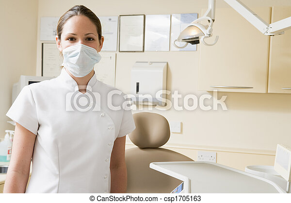 Dental assistant in exam room with mask on - csp1705163