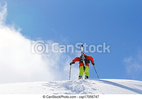 Skier climbing a snowy mountain - csp17056747