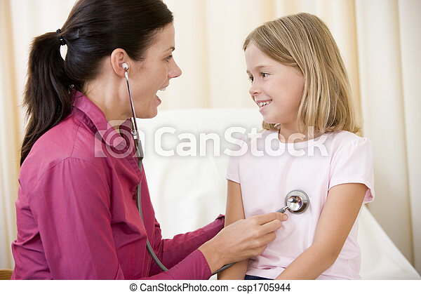 Doctor giving checkup with stethoscope to young girl in exam room smiling