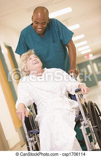 An Orderly Pushing A Senior Woman In A Wheelchair Down A Hospital Corridor - csp1706114