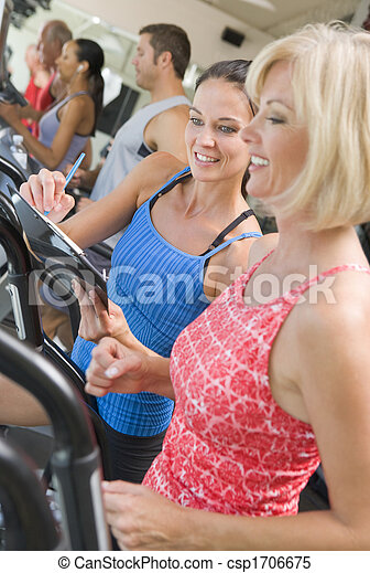 Personal Trainer Instructing Woman On Treadmill - csp1706675