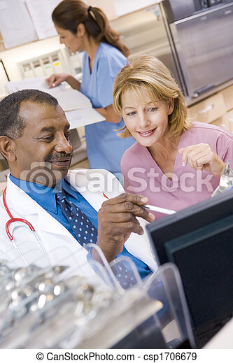 A Doctor And Nurse Discussing Something At The Reception Area Of A Hospital - csp1706679