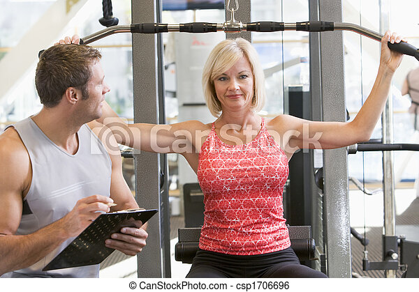 Personal Trainer Watching Woman Weight Train - csp1706696