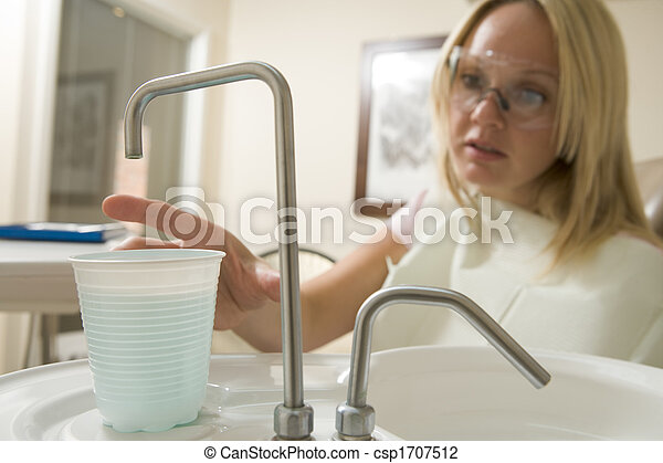 Woman in dental exam room reaching for water - csp1707512
