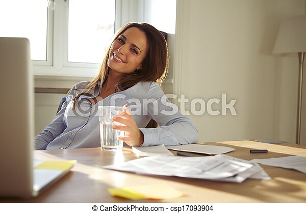 Woman working in home office smiling at camera - csp17093904