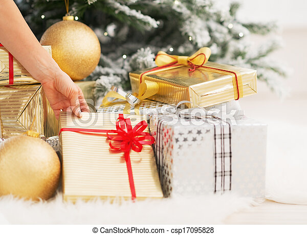 Closeup on woman taking christmas present box under christmas tree