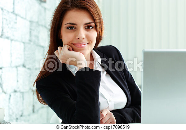 Young smiling businesswoman sitting at the table in office - csp17096519