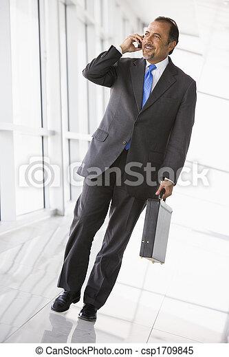 Businessman walking in corridor on cellular phone smiling (high key/selective focus) - csp1709845