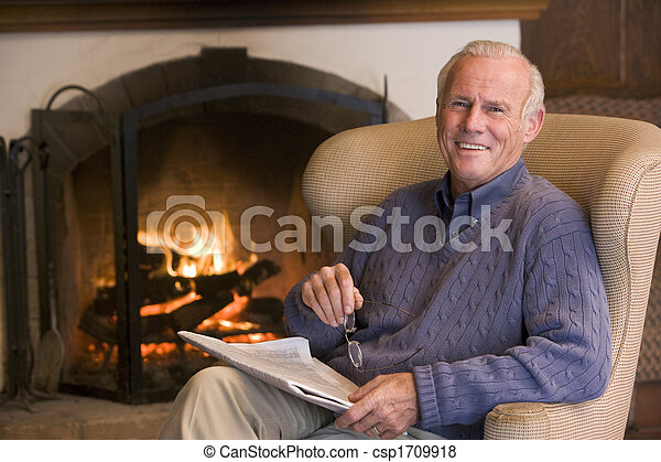 Man sitting in living room by fireplace with newspaper smiling - csp1709918