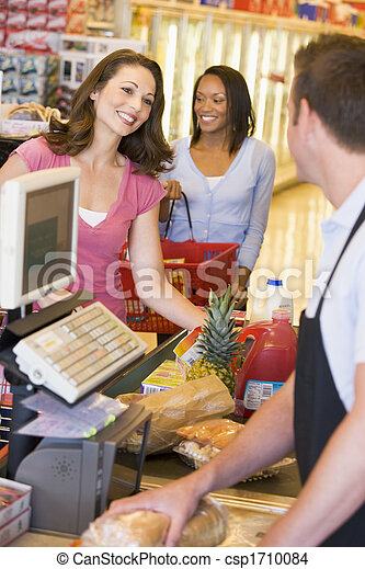 Women paying for purchases at a grocery store - csp1710084
