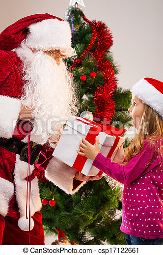 Little beautiful blond girl getting present from Santa Claus. Looking happy and surprise with Christmas tree on background