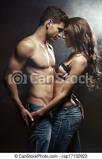 Beautiful young smiling couple in love embracing indoor - csp17132923