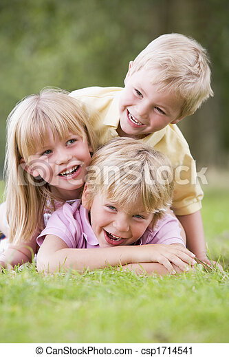 Three young children playing outdoors smiling - csp1714541
