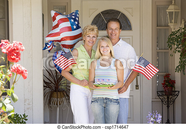 Family at front door on fourth of July with flags and cookies smiling