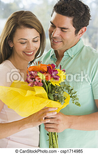 Husband giving wife flowers and smiling - csp1714985