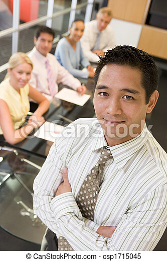Businessman with four businesspeople at boardroom table in background - csp1715045