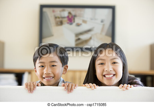 Two young children in living room with flat screen television smiling - csp1715085