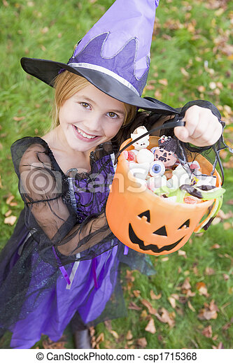 Young girl outdoors in witch costume on Halloween holding candy - csp1715368