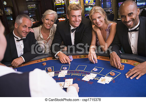 Five people in casino playing blackjack and smiling (selective focus) - csp1715378