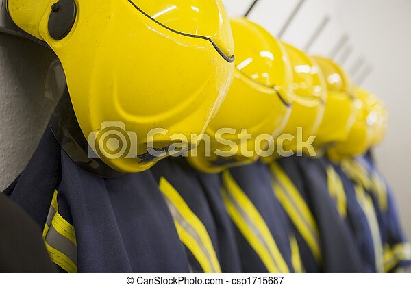 Line of firefighting uniforms hanging neatly on wall hooks (depth of field) - csp1715687