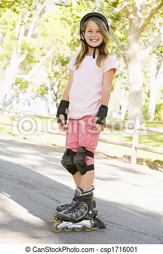 Young girl outdoors on inline skates smiling - csp1716001