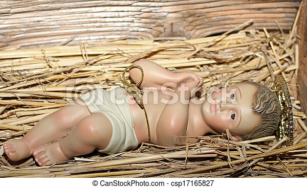 Baby Jesus is laid in the cradle in a manger - csp17165827