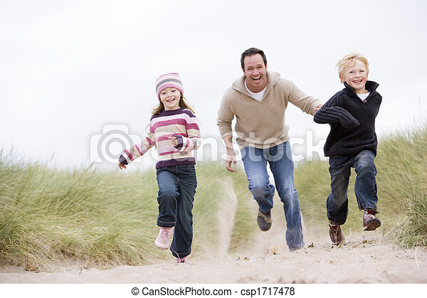 Father and two young children running at beach smiling - csp1717478