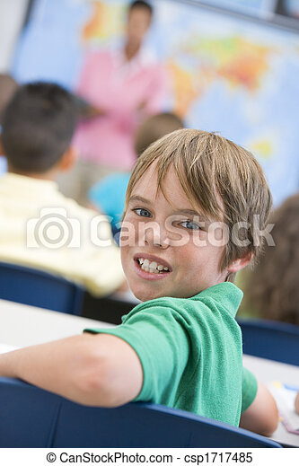 Student in class looking at camera with teacher in background (selective focus) - csp1717485