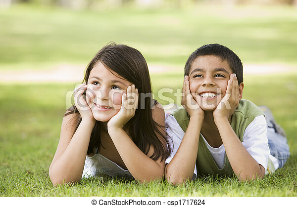 Two young children outdoors lying in park smiling (selective focus) - csp1717624