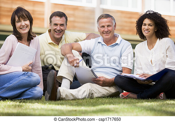 Adult students on lawn of school with notebooks - csp1717650