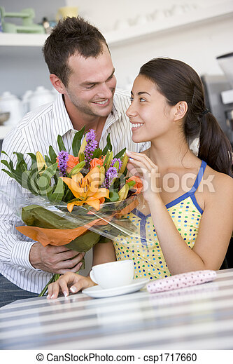 Young man giving a bouquet of flowers to a young girl sitting at a table