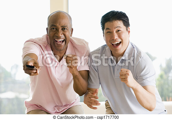 Two men in living room with remote control cheering and smiling - csp1717700