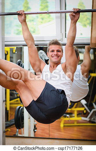 Smiling young man hanging from gym equipment - csp17177126