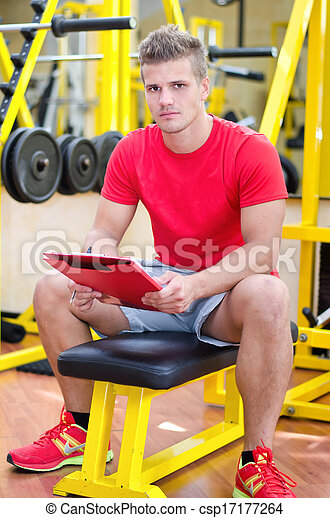 Young male personal trainer holding clipboard - csp17177264