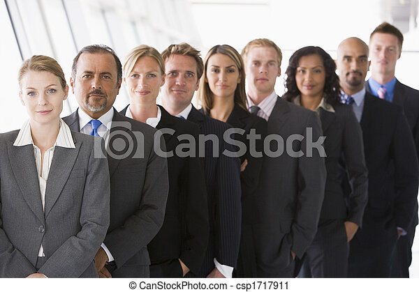 Group of co-workers standing in office space smiling (high key/depth of field) - csp1717911