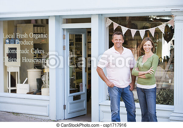 Couple standing in front of organic food store smiling - csp1717916