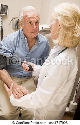 Doctor Measuring Mans Blood Pressure - csp1717926