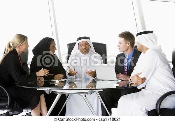 Five businesspeople in office with laptop talking and smiling (high key/selective focus) - csp1718021