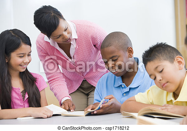 Students in class reading with teacher helping (selective focus) - csp1718212