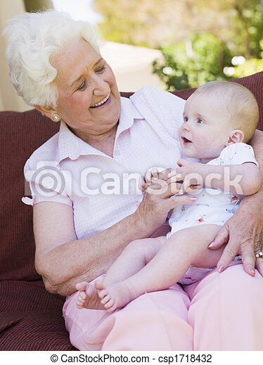Grandmother outdoors on patio with baby smiling - csp1718432